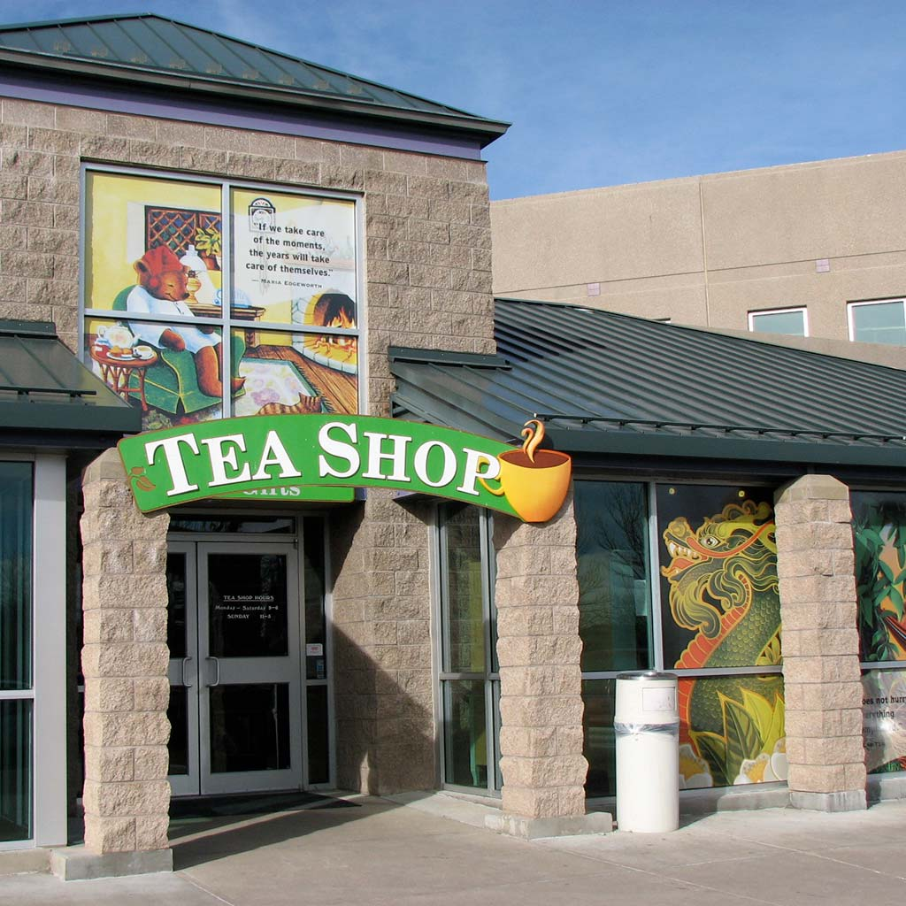 Storefront with a logo and overhanging green sign that reads TEA SHOP