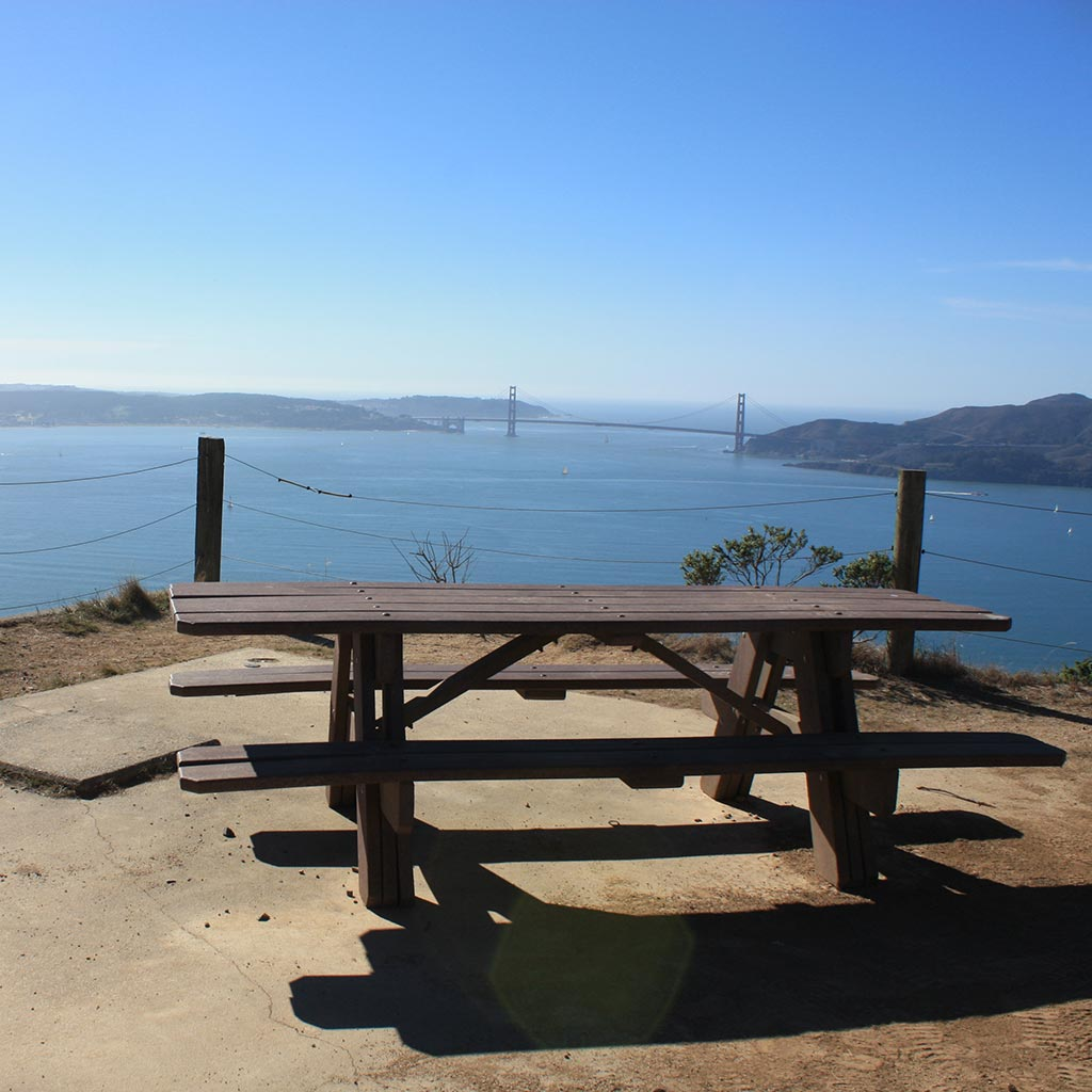 A picnic bench overlooks a stunning vista of the Bay with the Golden Gate bridge looming in the background. Taken at Angel Island State Park campsite.