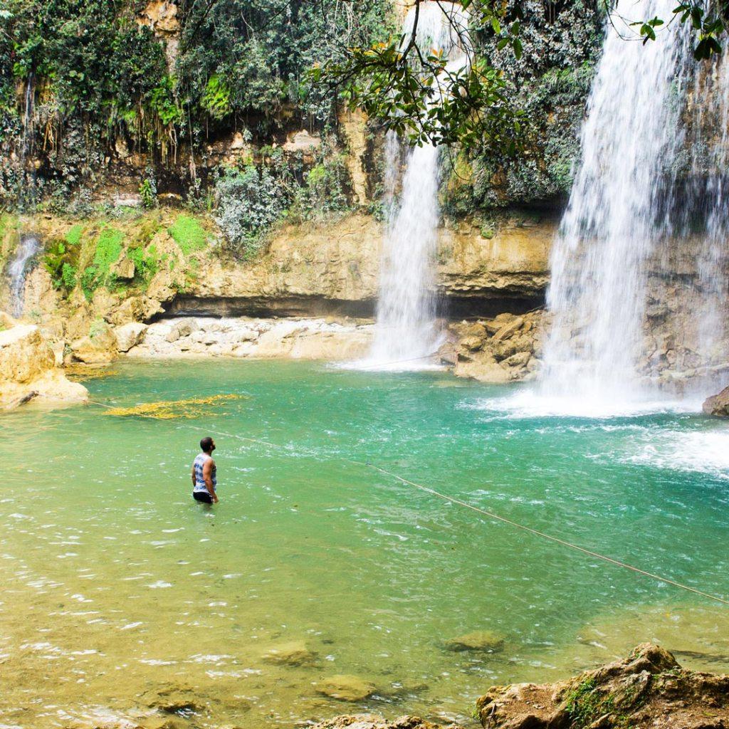 a man standing in green waters near 3 roaring waterfalls