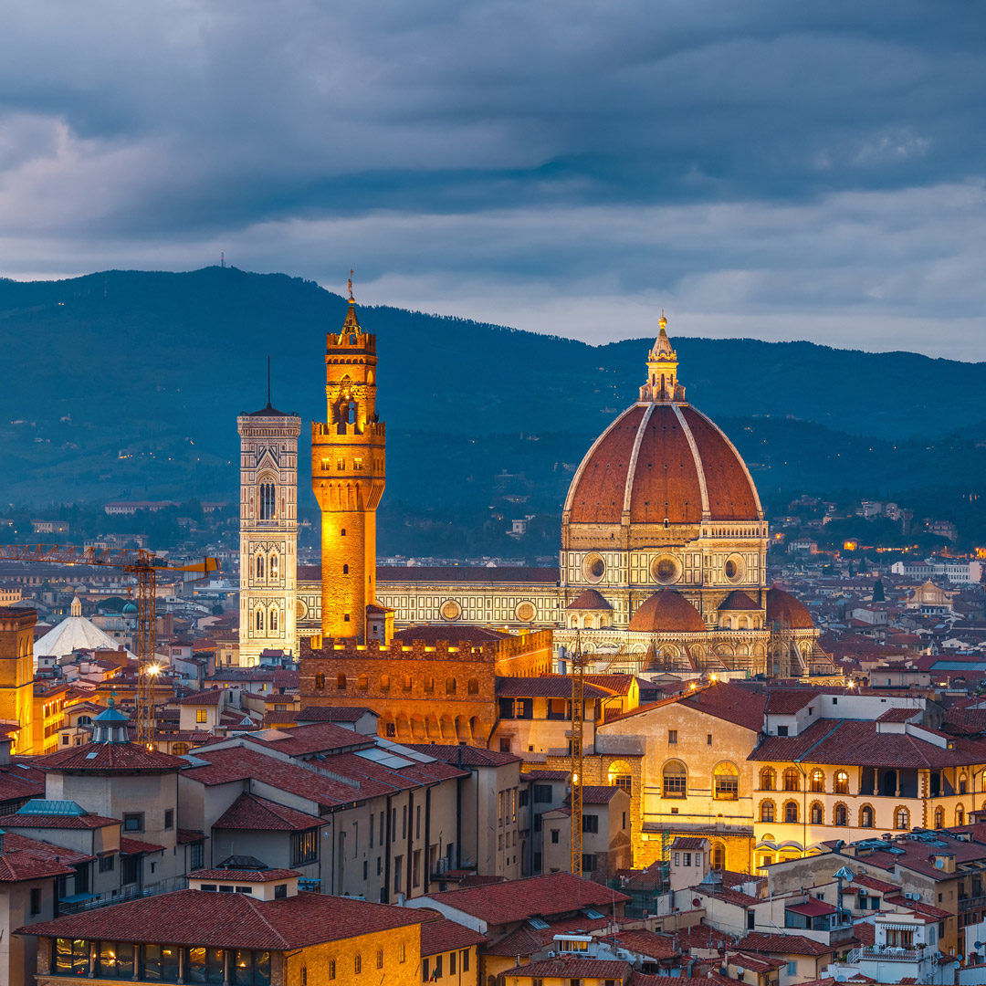 Rooftops and Duomo of Florence lit by city lights at dusk