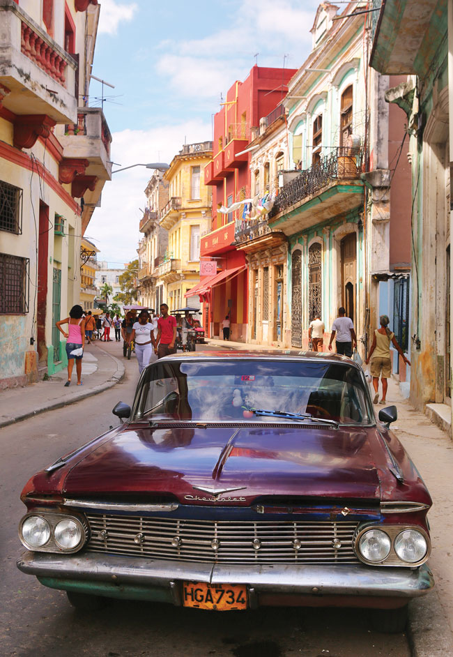 A deep purple chevy parked on the street amidst colorful buildings in Havana.