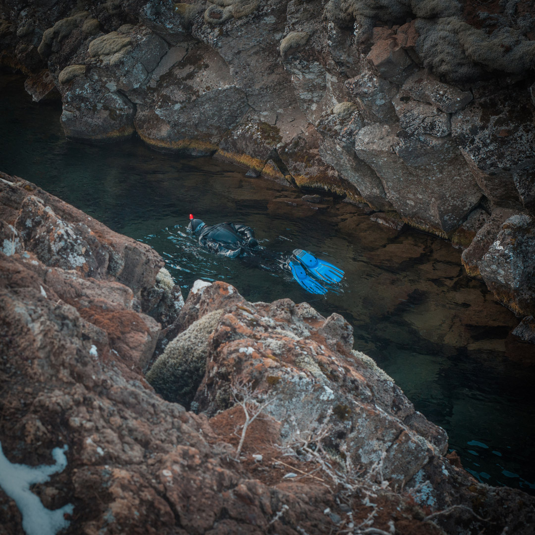 a person snorkeling in a fissure in Thingvellir National Park