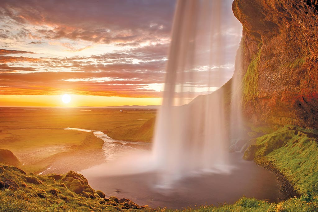 Two of Iceland's natural wonders–the midnight sun and waterfalls. Photo © Phyletto/Dreamstime.