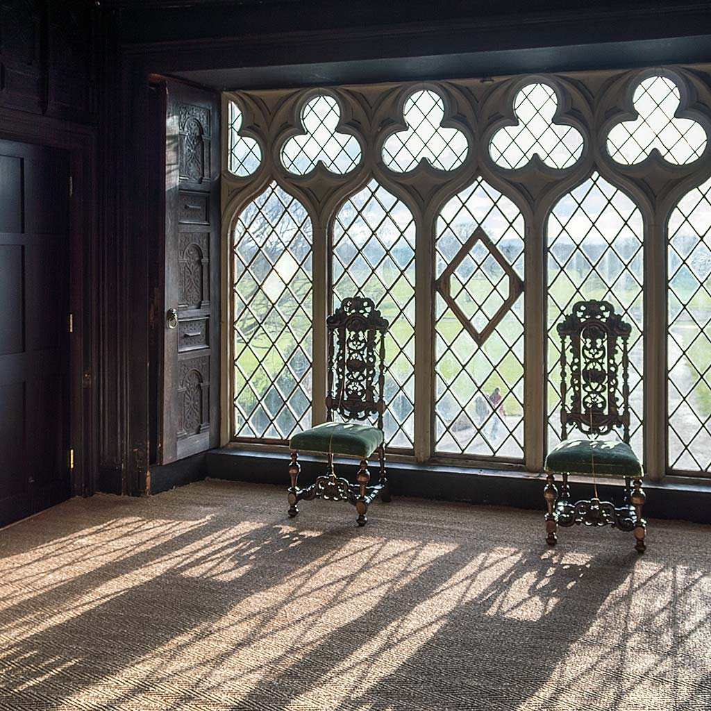 Elaborate chairs in front of a wall of diamond-paned windows inside Malahide castle in Dublin.