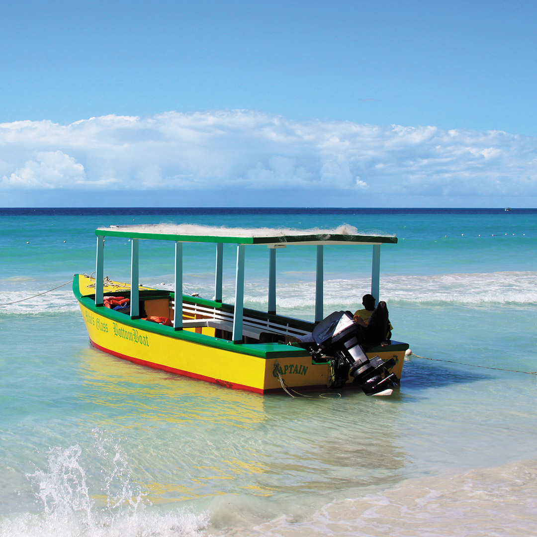 a yellow boat along the shore of Seven Mile Beach in Jamaica