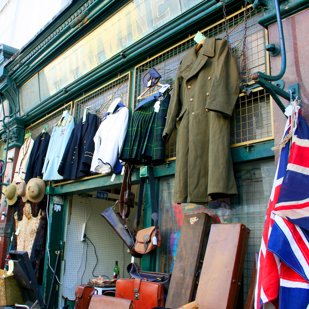vintage military coat hangs with other items in the Portobello Market in London