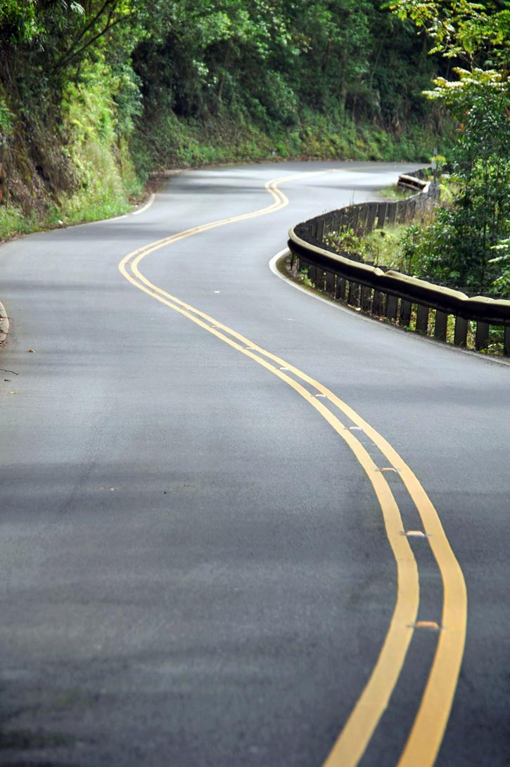 The curving two-lane Road to Hana flanked by lush vegetation.