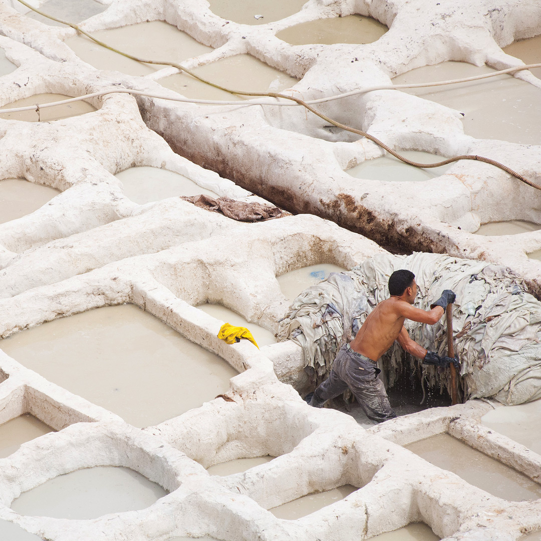 a man works in a tannery in Morocco