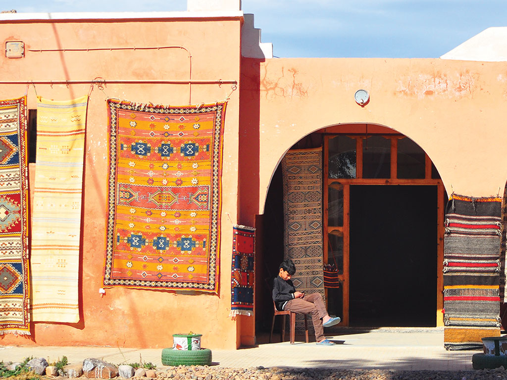 a boy sitting on a chair outside a rug shop draped in rugs