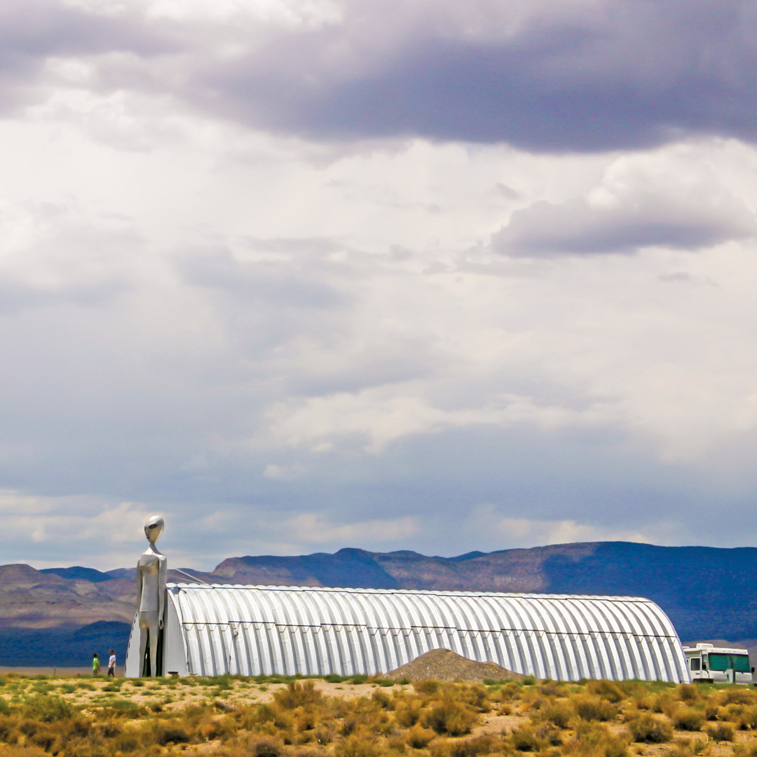 quanset hut next to a large alien figure in Nevada