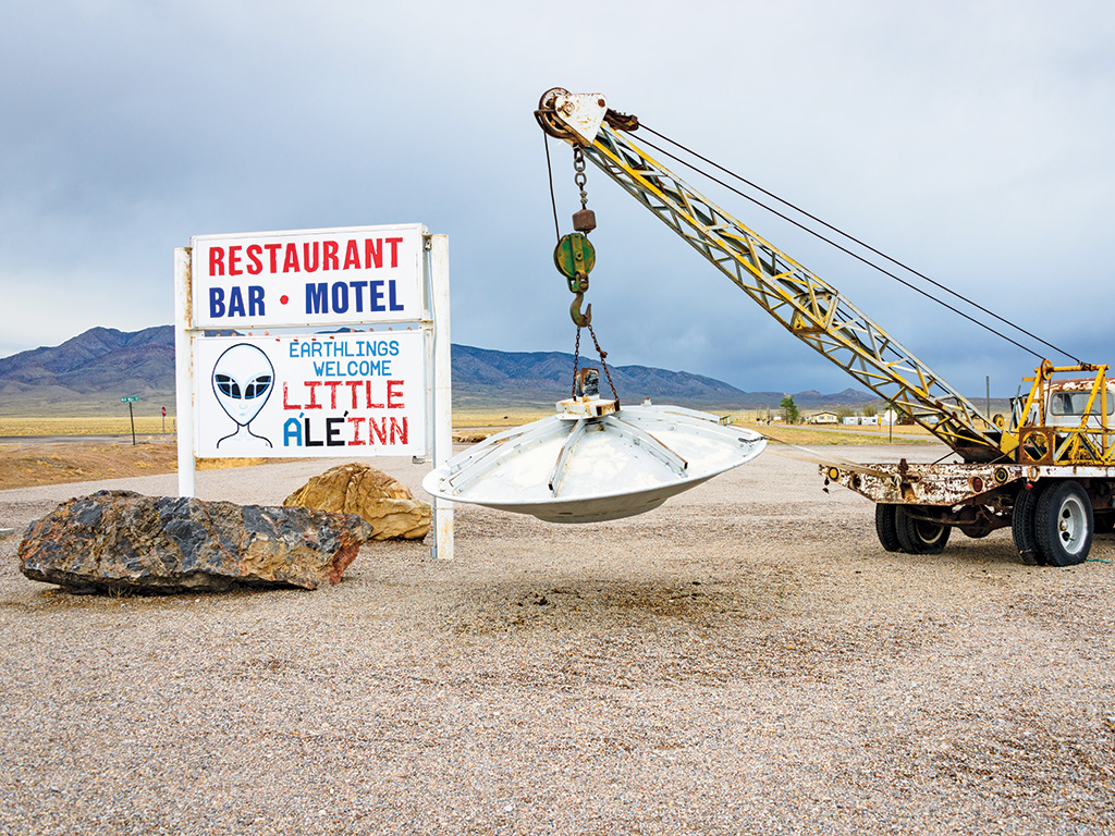 truck with a crane holding up a flying saucer sculpture next to a welcome sign in Nevada