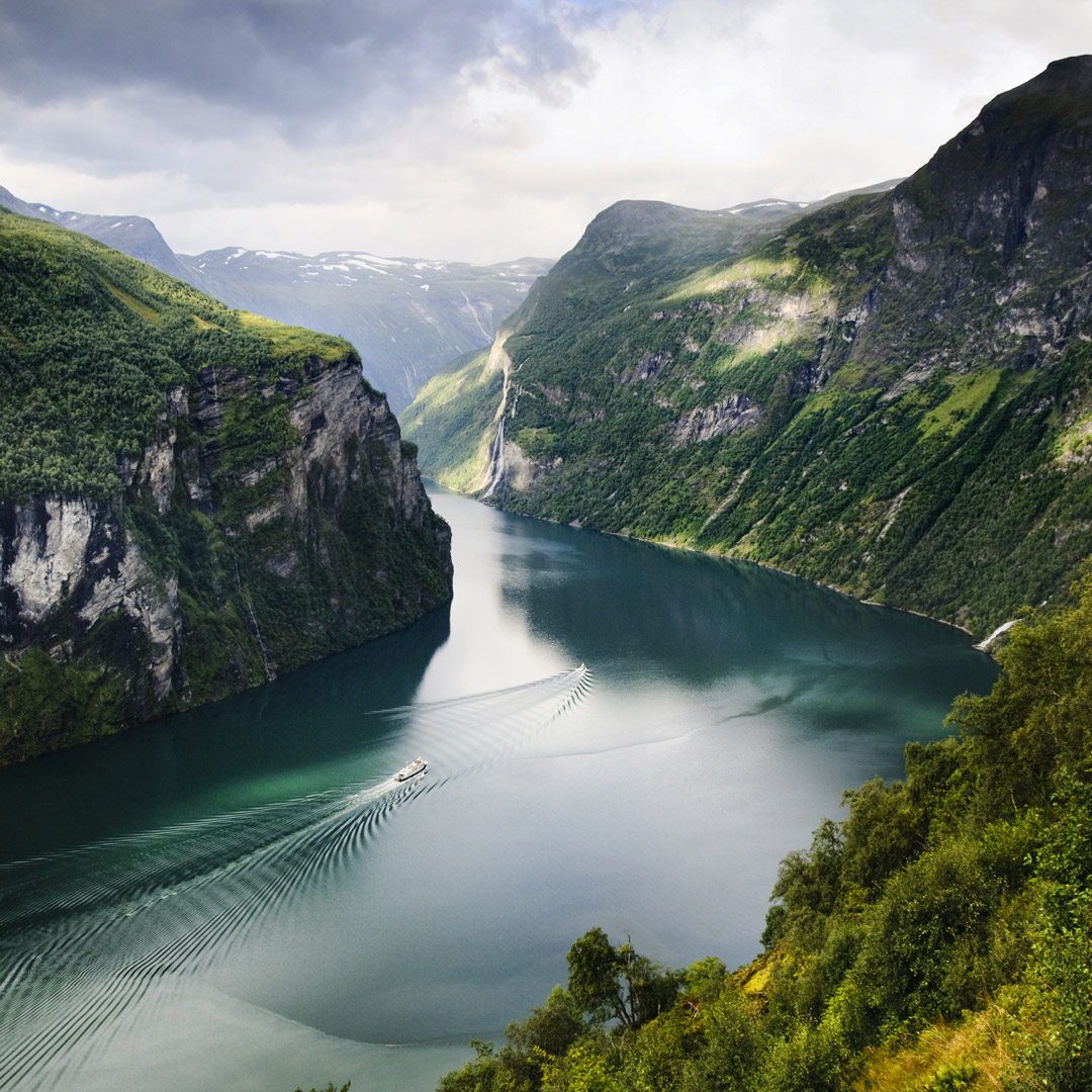 Cruise ship sails through the deep blue-green waters of Geirangerfjord