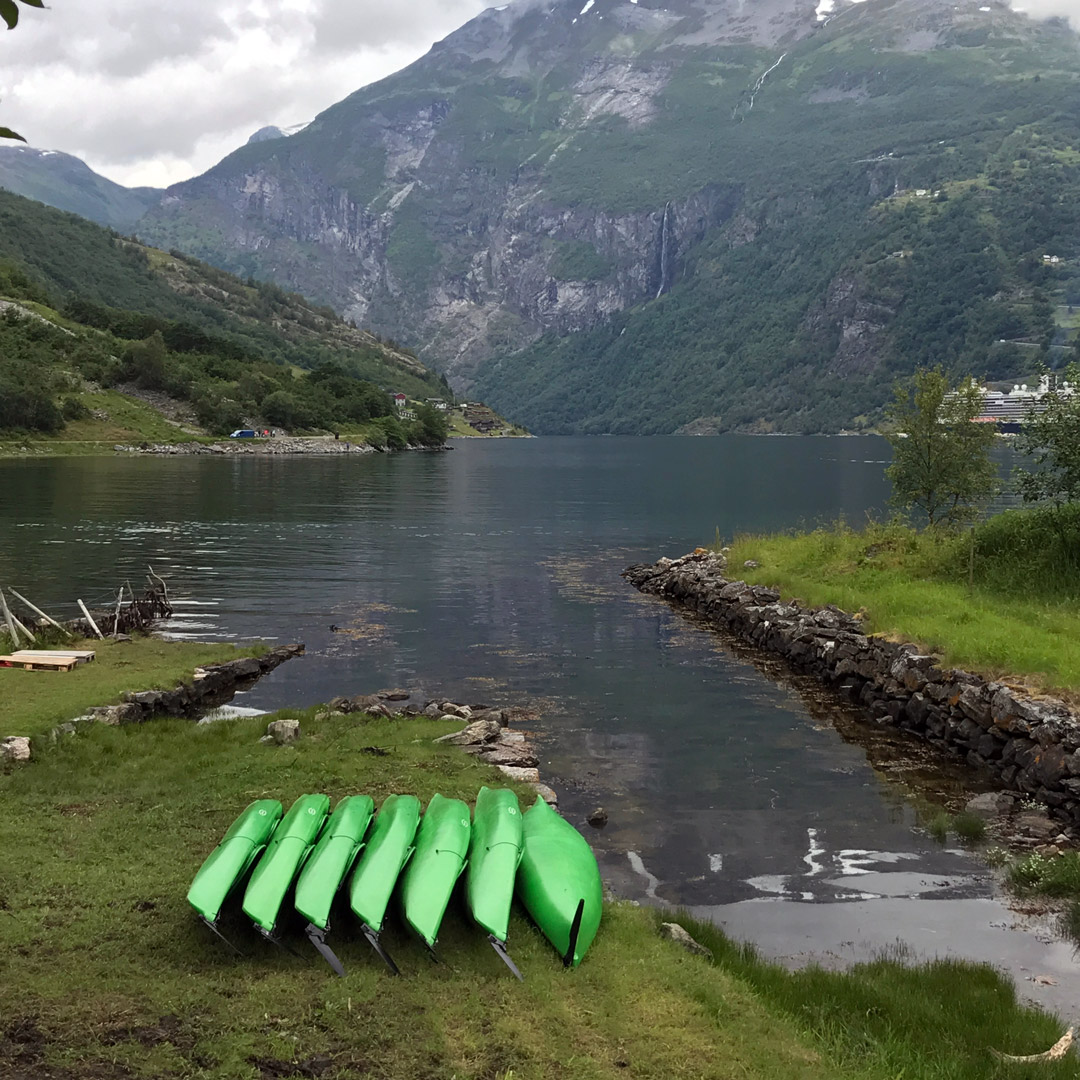 bright green kayaks on the shore near Geirangerfjord in Norway