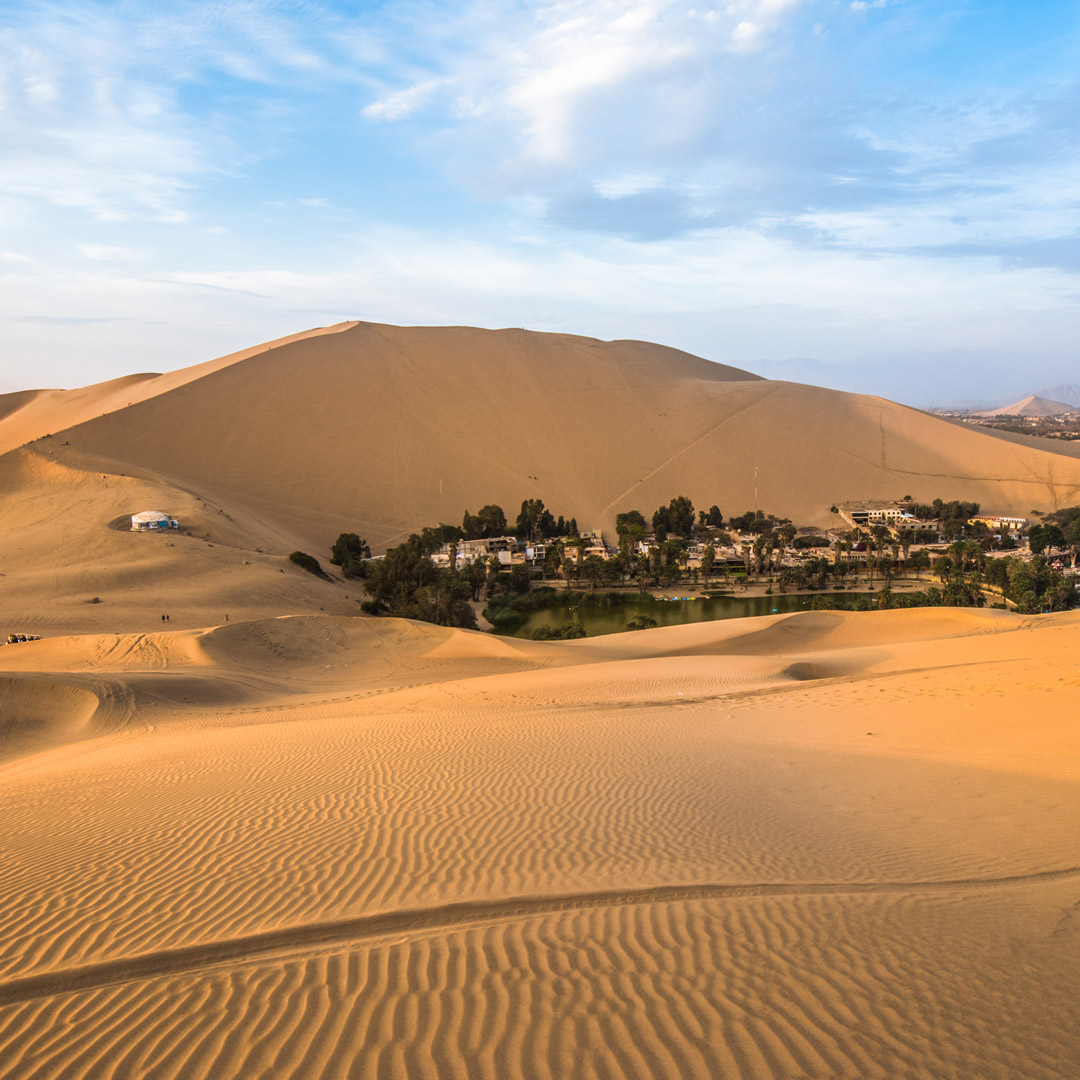 sand dunes surround a lagoon and village