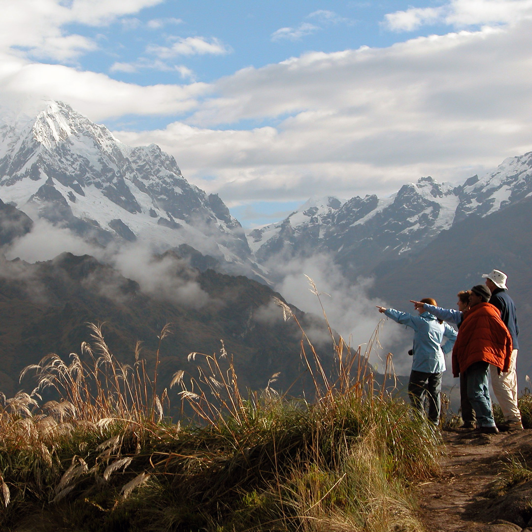 3 people stand on a mountain admiring the peaks of the Urubamba Range along Peru's Inca Trail