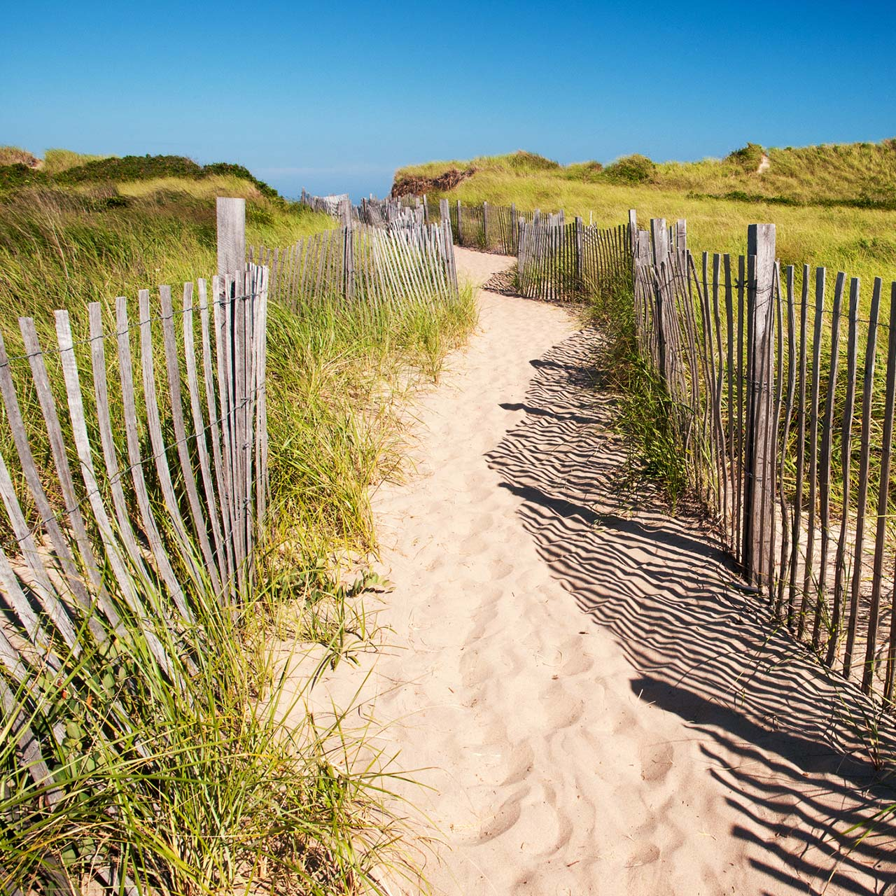 A sandy path lined by a wooden fence at Block Island's Crescent Beach.