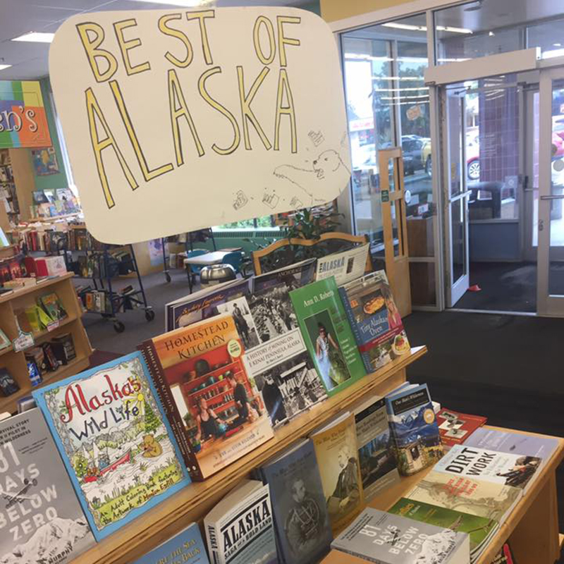 """Books are displayed, outwards facing, on a shelf with a handmade sign that says """"Best of Alaska"""" above them. The exterior of the store is somewhat visible behind"""