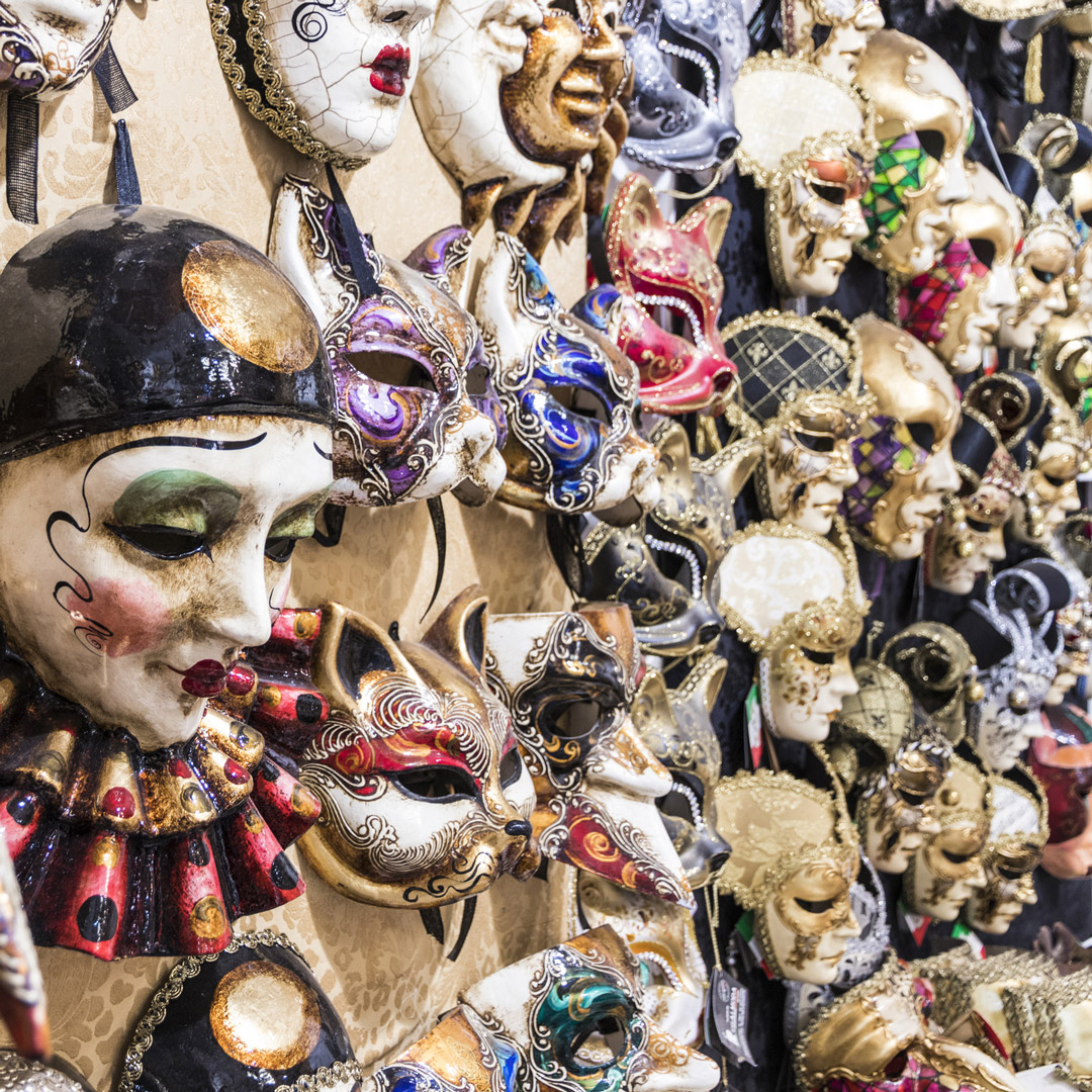 a variety of colorful Italian masks on display