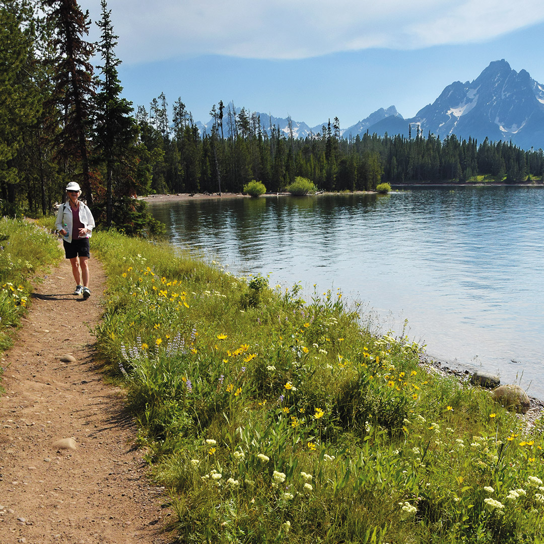woman walking on a trail next to a lake in Wyoming