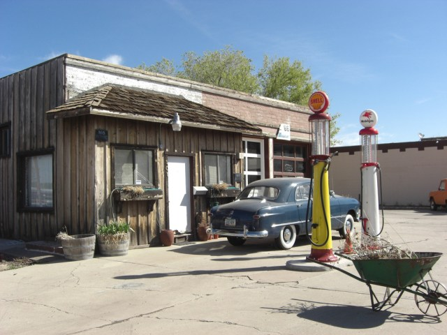 A small museum formerly a gas station with the original pumps and a classic 50s car out front.