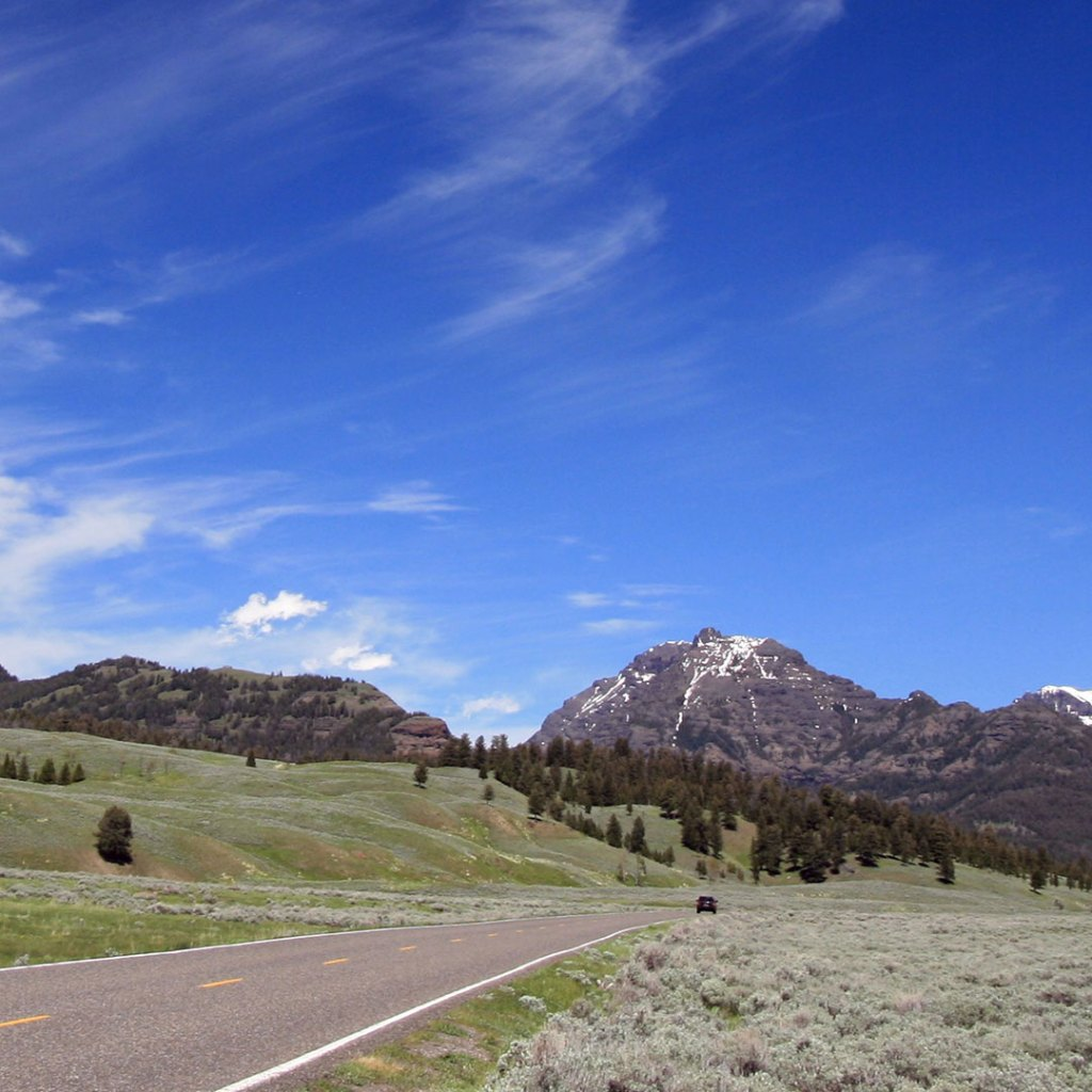 blue sky over a road leading toward the mountains in Yellowstone