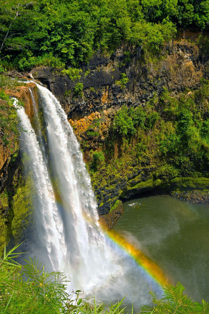Wailua falls plunging over the cliffside with a rainbow forming in the mist.