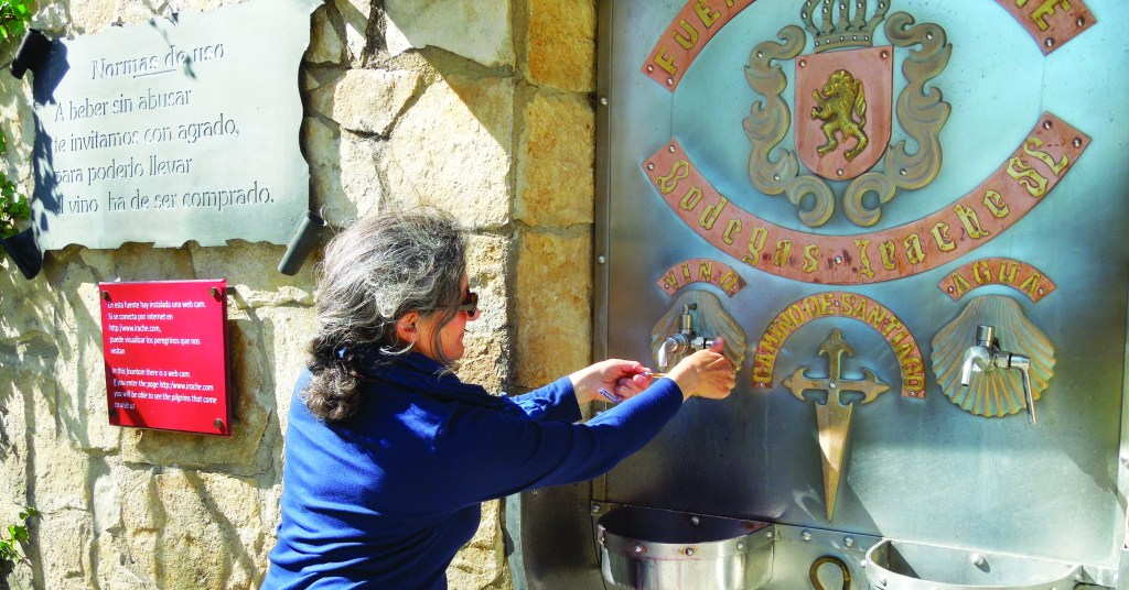 a woman fills her scallop shell from a wine fountain