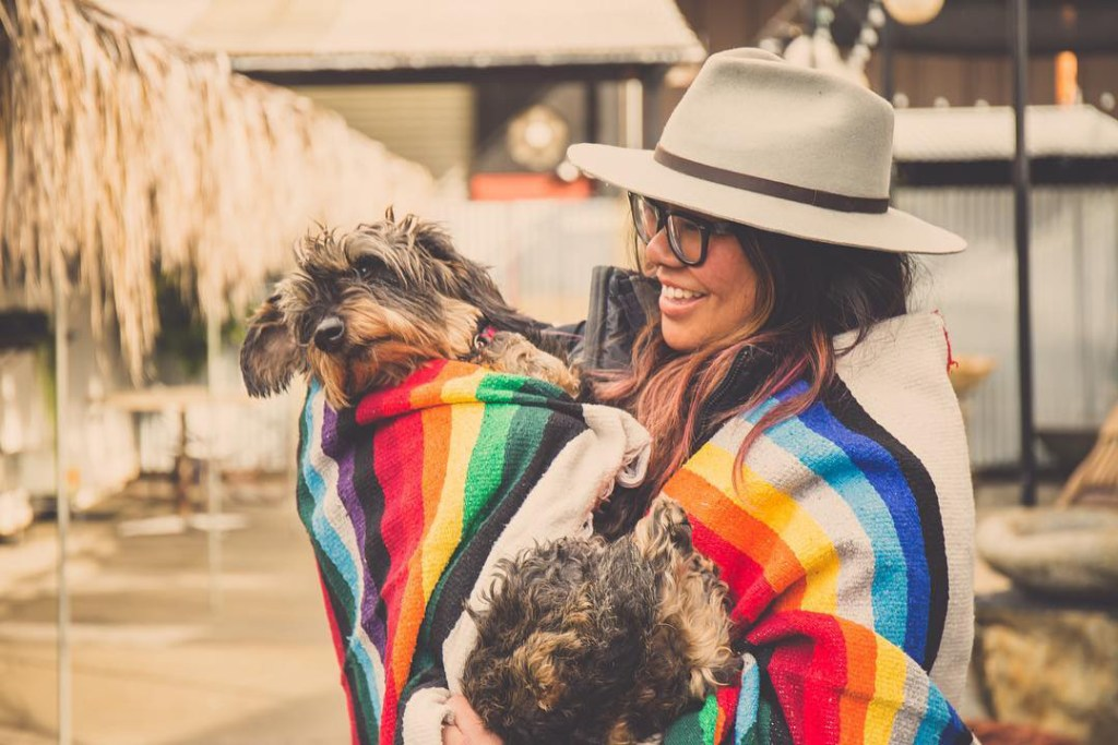 Angie Chua holding dog in a rainbow blanket