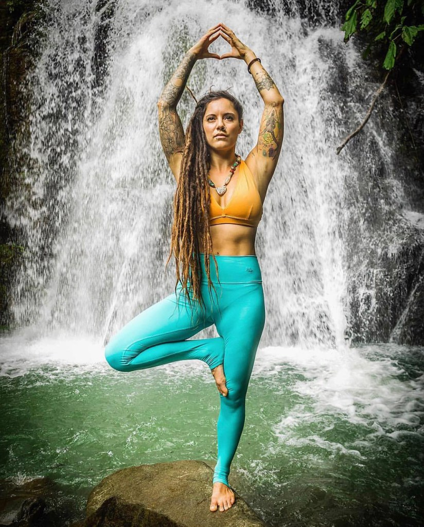 Stephanie Góngora doing yoga under a waterfall in Costa Rica