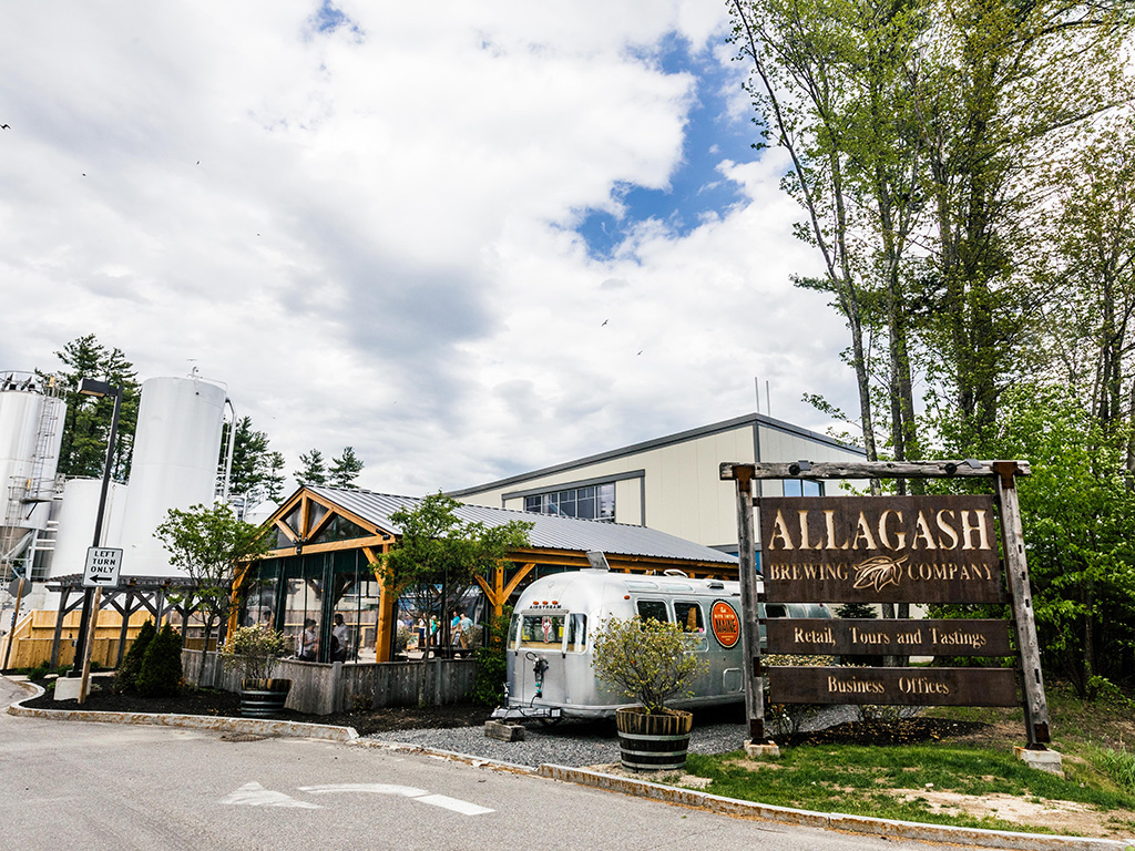 brewery building with a wooden sign and a trailer in front
