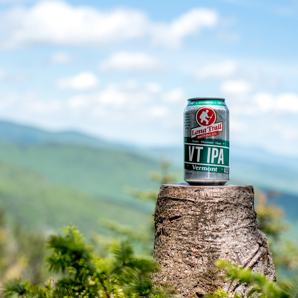 a beer can sitting on a tree stump