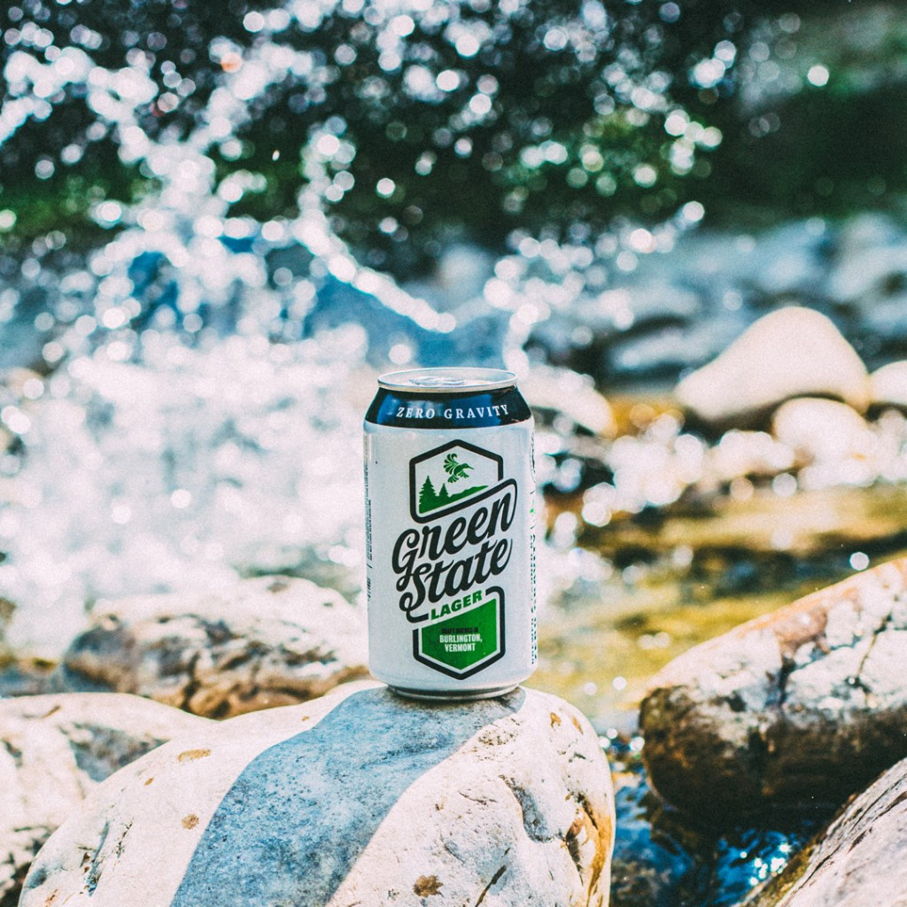 a beer can on a rock with water splashing in the background