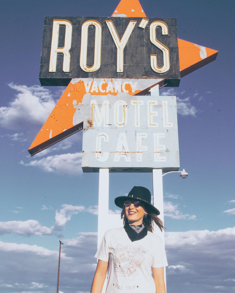 woman in a black hat posing in front of a faded hotel sign on route 66 with blue sky in the background
