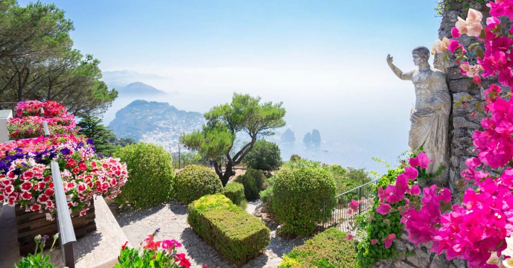 Pink flowers and the statue of a man overlook the island coastline of Capri.