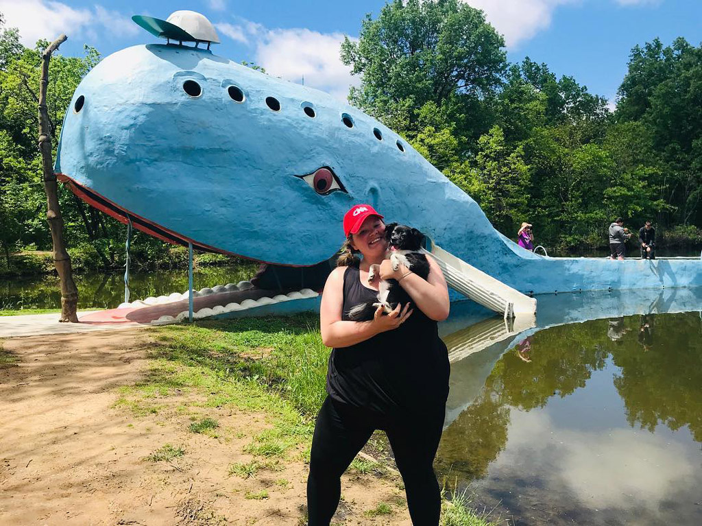 woman wearing black holding a dog in front of a constructed blue whale in Oklahoma
