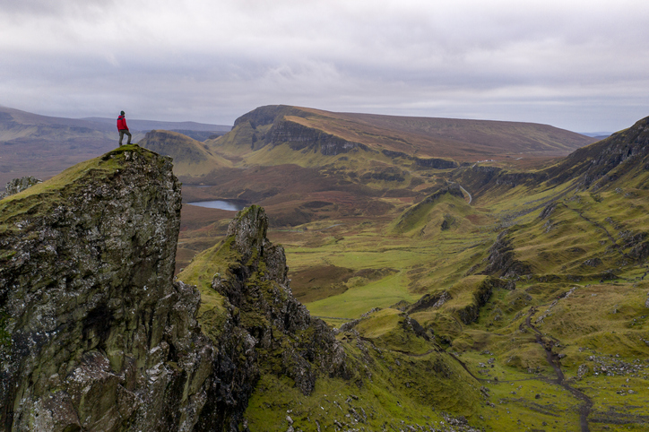 Hiker standing on mountain top in rugged volcanic landscape around Old Man of Storr, Isle of Skye, Scotland