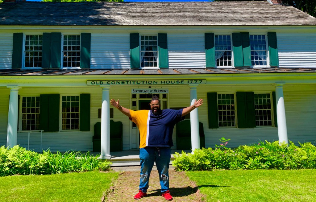 a Black plus-size man spreading his arms wide standing in from of an historic building in windsor, vermont