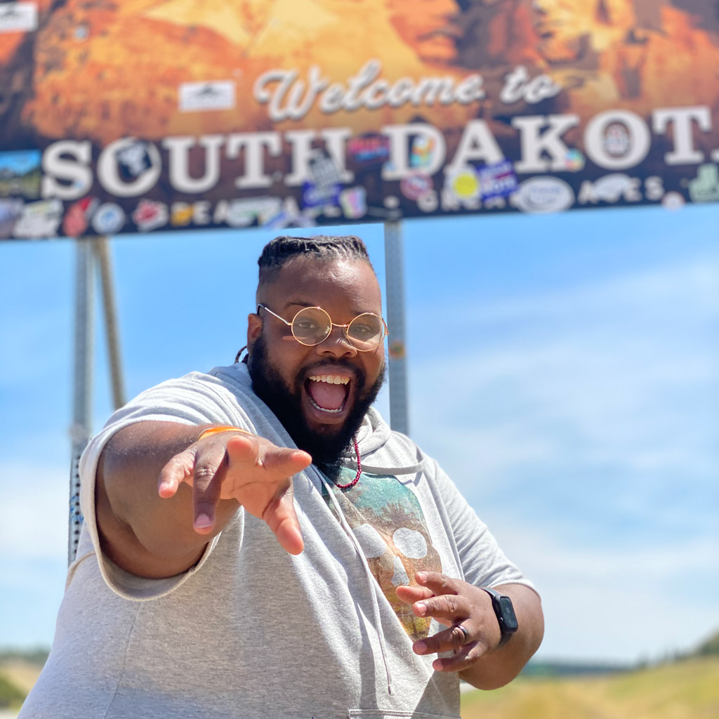 happy black plus size man in front of a South Dakota sign