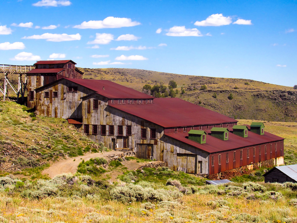 photo of a gold mine in South Pass City Wyoming with a red roof and clear skies.