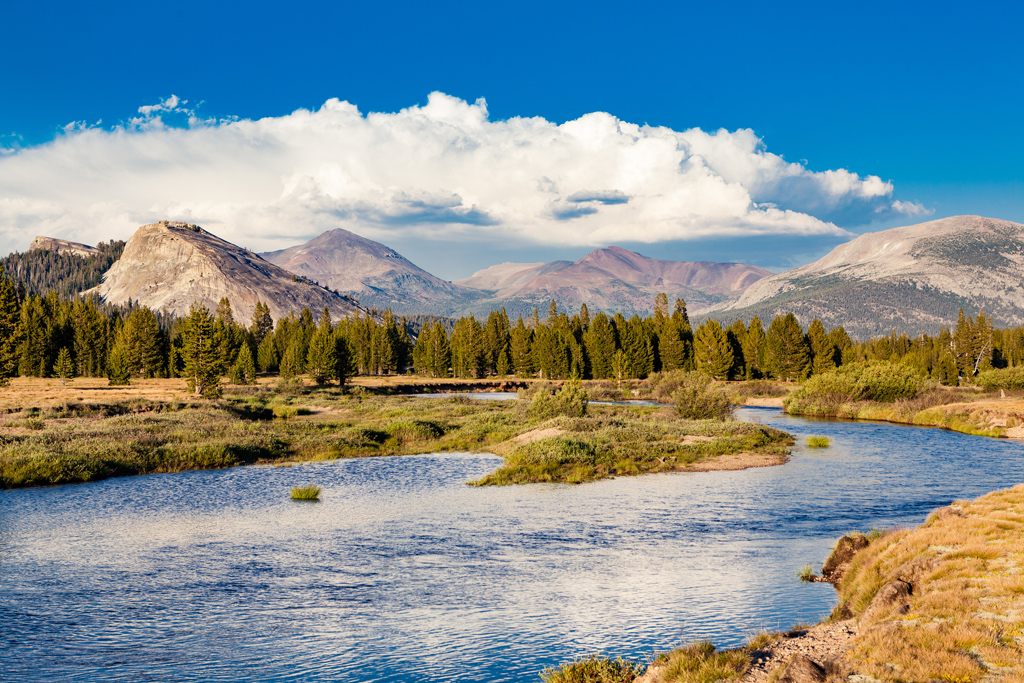 Tuolumne Meadows in Yosemite National Park, California with clear blue water and clouds.