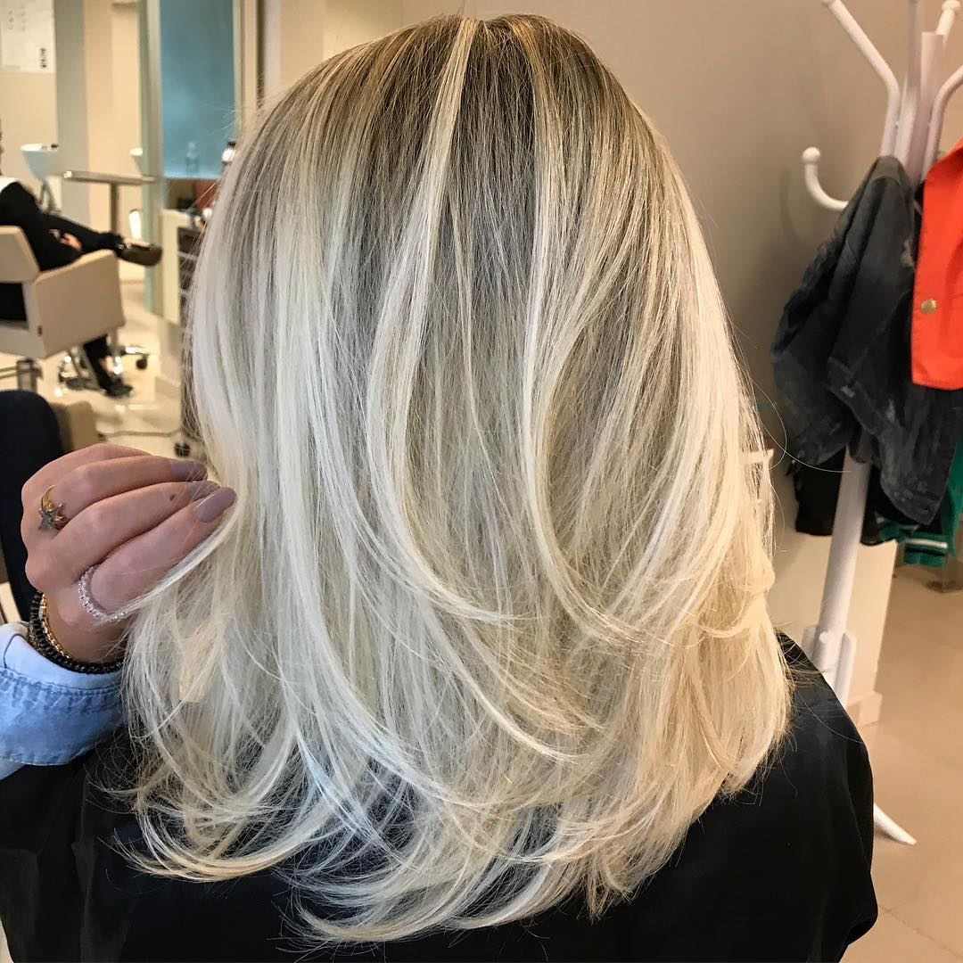 Medium Blonde Layered Hair with Dark Roots