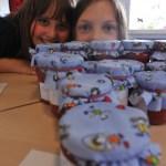 Hannah und Chiara verkaufen selbst hergestellte Erdbeermarmelade in vier Varianten.