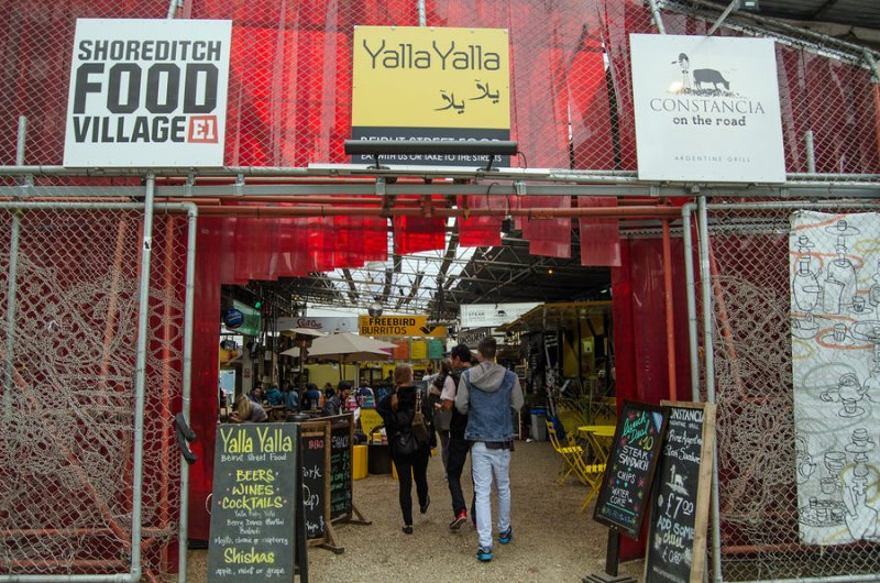LONDON, UNITED KINGDOM - AUGUST 30, 2014: Fashionable visitors entering the outdoor Shoreditch Food Village in the hip district of Hackney in London's East End.