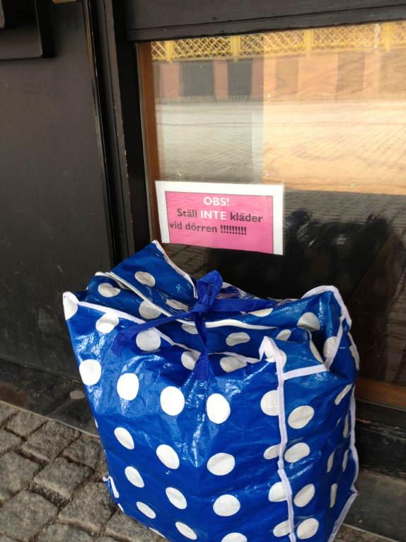 Kasse med kläder utanför dörr med anslaget: OBS! Ställ INTE kläder vid dörren !!!!!!!!!