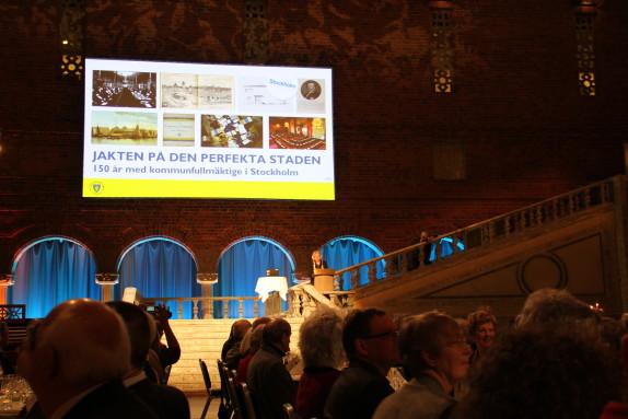 Margareta Björk talar vid en bild av firandets hemsida