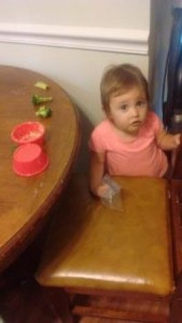 A 1-year old spreads hummus on the table.