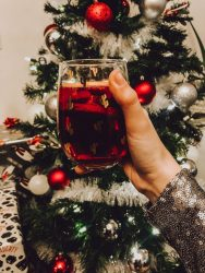 Holding a glass of sangria in front of the Christmas tree.