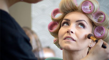 Client in rollers having her make up done professionally