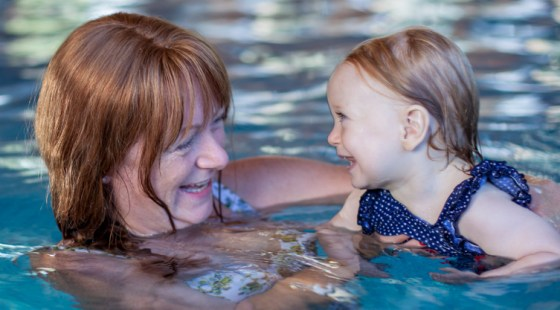 smiling client with baby in swimming pool