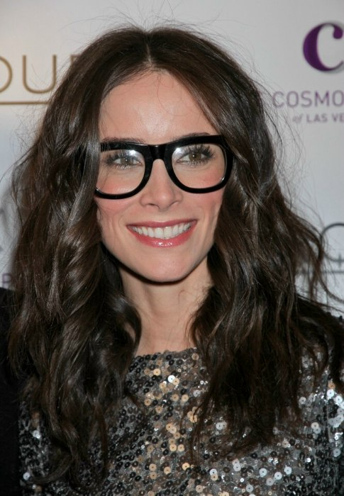 Abigail Spencer wearing jumbo black glasses and with her long hair parted in the center